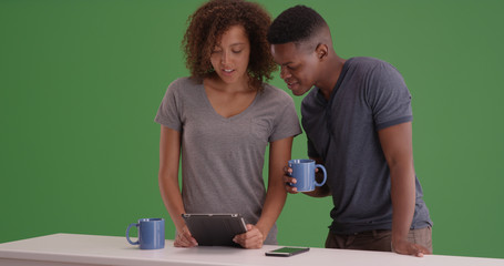 Black millennial couple drinking coffee and using tablet on green screen