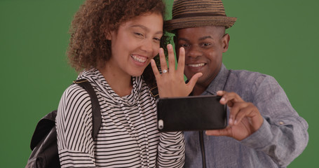 Newly engaged black couple taking selfie with phone on green screen