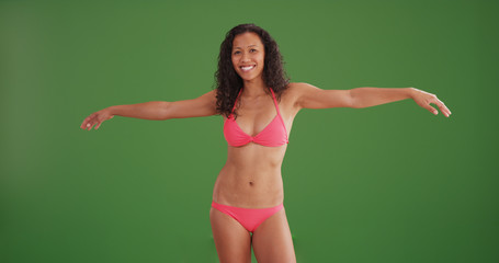 Happy mixed race woman wearing bikini with arms outstretched on green screen