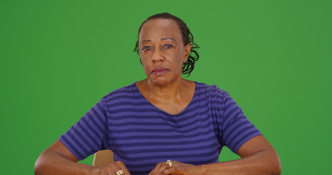 Serious looking old black lady sitting and looking at camera on green screen
