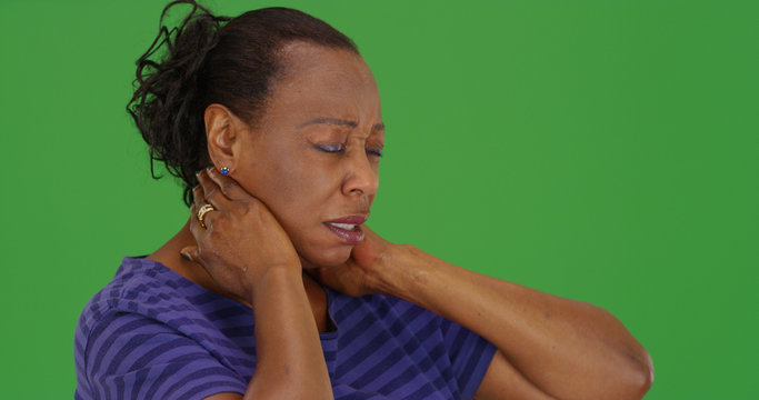 Mature black woman with bad neck pain on green screen