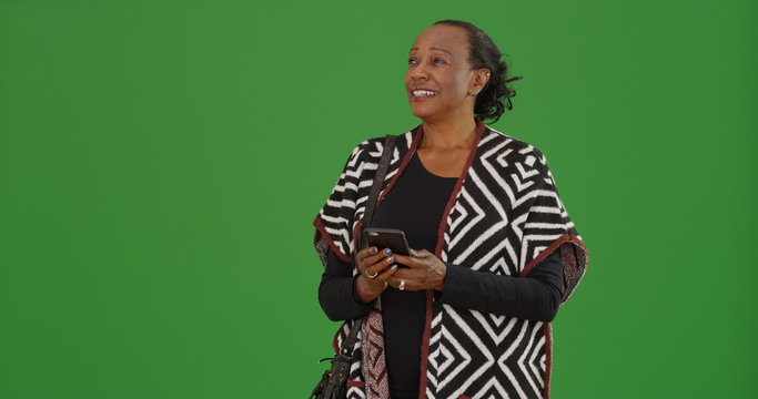 Happy old stylish black woman using phone on green screen