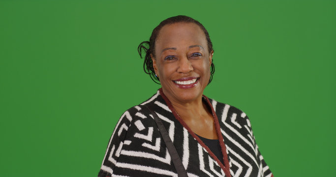 Happy older black woman poses for a portrait on green screen