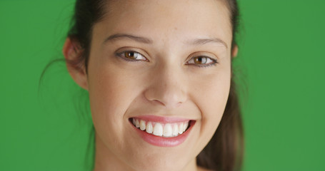 Close-up of smiling young brunette female looking at camera on green screen