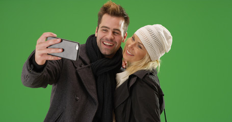 Young happy couple taking selfies with phone together on green screen
