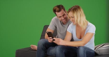 White girlfriend showing boyfriend video on smartphone on green screen