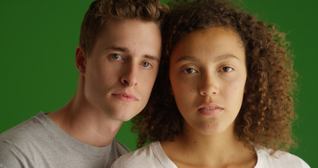 Close up portrait of serious young couple looking at camera on green screen