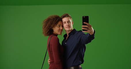 Happy interracial couple using smartphone to take selfie on green screen
