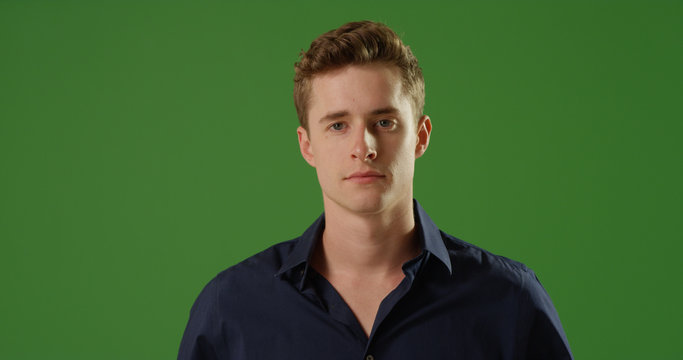 Handsome young Caucasian man looking at camera on green screen