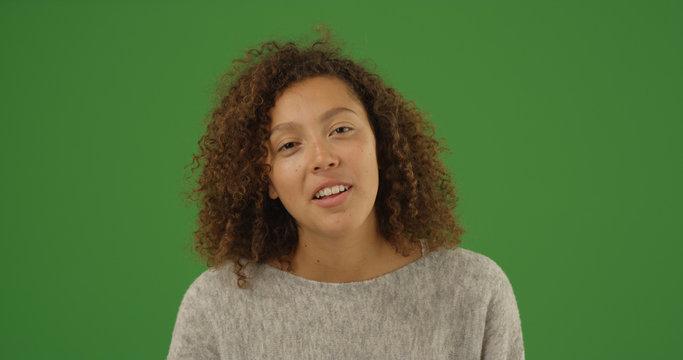 Cute black millennial female looking at camera on green screen