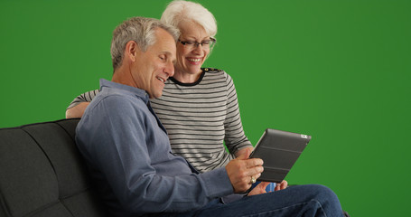 Senior couple sitting on couch watching video on tablet on green screen