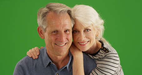 Happy elderly Caucasian couple posing together on green screen