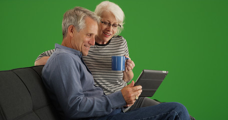 Modern senior couple sitting on couch with tablet on green screen
