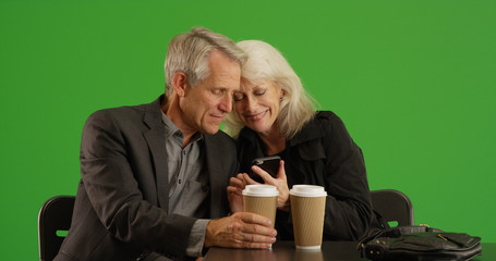 Senior woman showing her date photos on smartphone at cafe on green screen