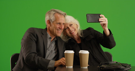 Senior couple out on date taking selfie with smartphone on green screen