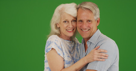 Smiling senior couple hugging and looking at camera on green screen