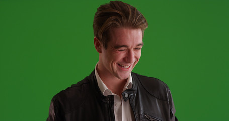 Portrait of Caucasian male in leather jacket laughing on green screen