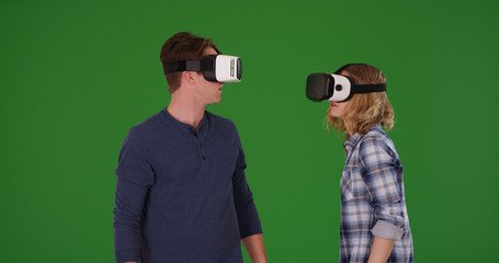 Caucasian male and female wearing VR headsets having fun on green screen