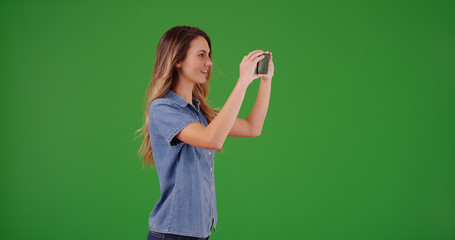 Attractive white female taking picture with phone camera on green screen