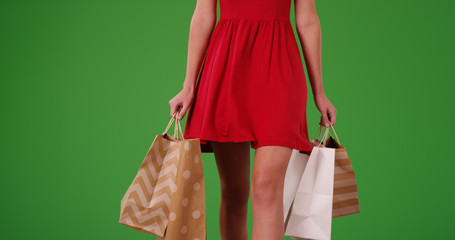 Closeup of female shopper's lower body with shopping bags on green screen