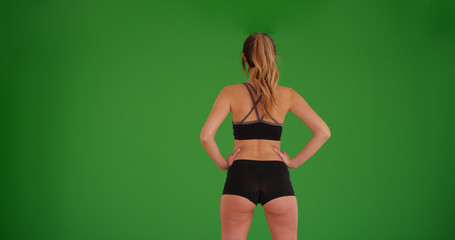 Rear view of fit athletic woman in sports bra standing on green screen
