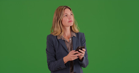 White businesswoman texting on mobile device on green screen