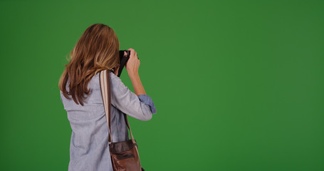 Rear view of blonde woman taking photo with camera on green screen