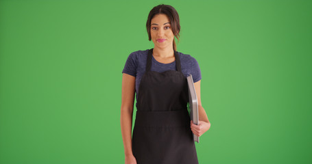 Smiling Hispanic woman wearing apron posing with baking sheet on green screen