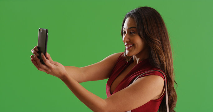 Attractive Latina female taking smartphone selfie on green screen