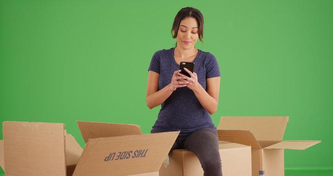 Latina woman taking break while unpacking boxes using phone on green screen