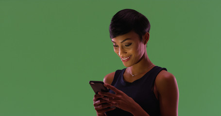 Portrait of African American female texting on smartphone on green screen