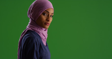 Black female in hijab looking at camera with serious expression on green screen