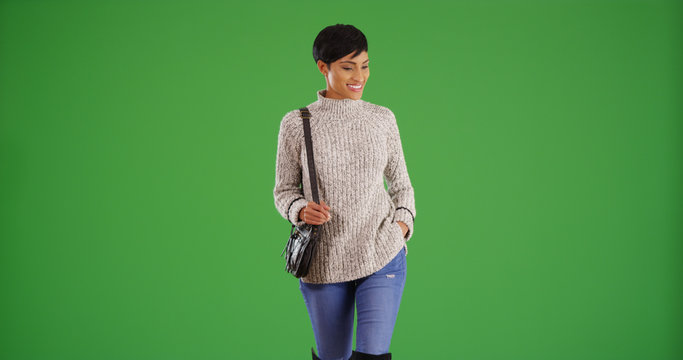 Beautiful young black woman with a purse walking on green screen
