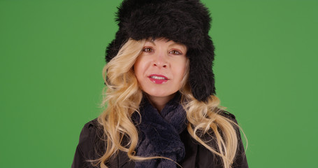 Stylish white woman wearing winter clothes looking at camera on green screen