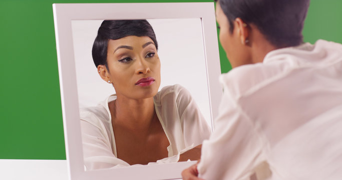Lovely black woman looking at her reflection in mirror on green screen