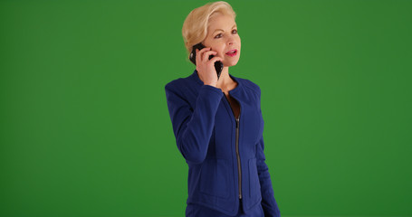 Professional white businesswoman making phone call on green screen