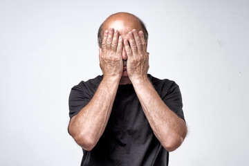 Mature caucasian man in black t-shirt covering his face with hands over gray background.