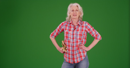 Mature farm woman with gardening gloves posing confidently on green screen