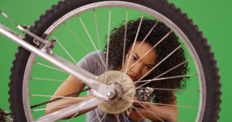 Handy black female doing repairs on her bicycle on green screen