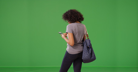 Rear view of casual black woman using mobile device to text on green screen