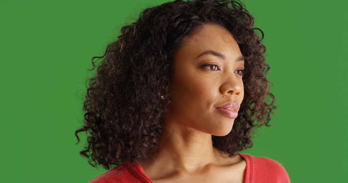 Pensive young black woman looking away from camera on green screen