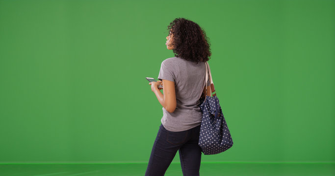 Rear view of black woman texting on smartphone on green screen