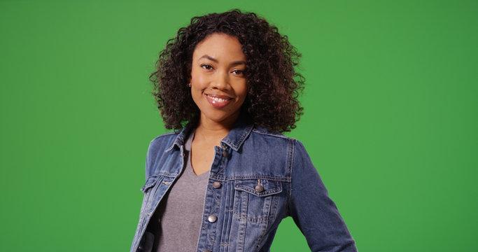 Portrait of happy black woman in jean jacket posing on green screen