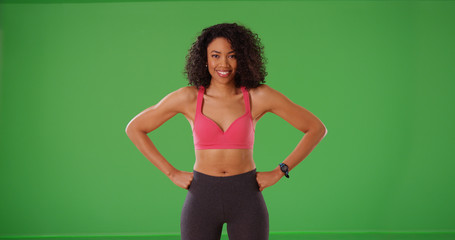 Smiling black athlete posing with hands at hips smiling on green screen