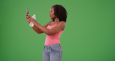 Pretty black woman with water bottle taking picture with phone on green screen