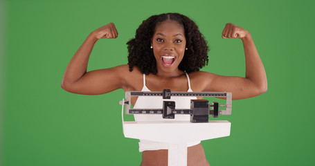 Healthy black female flexing arms for camera standing on scale on green screen