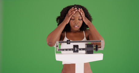 Young black woman weighing herself disappointed at weight gain on green screen