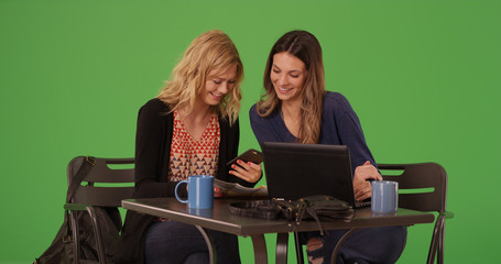 Pair of pretty women laughing at cafe using phone and laptop on green screen