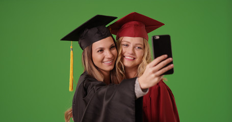 Couple of young female college graduates taking selfie on green screen
