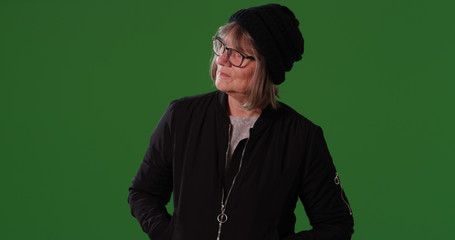 Casual old woman in jacket and beanie looking around on green screen